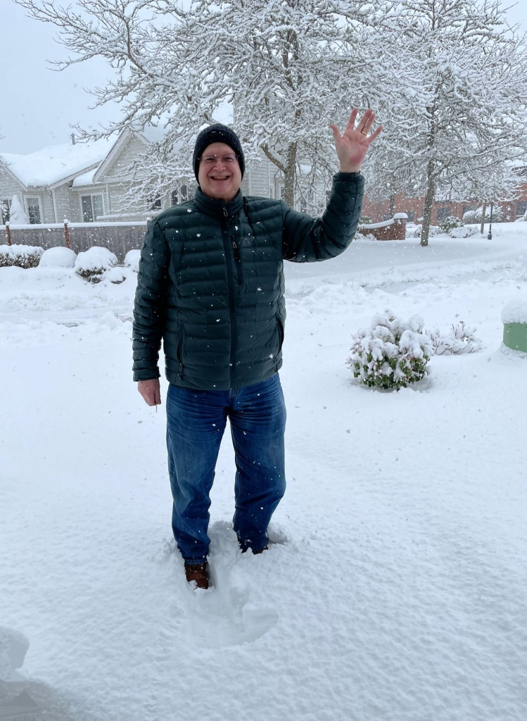 man standing in snow, waving, while snow continues to fall